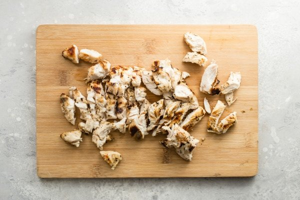 A wooden cutting board with chopped chicken on it.