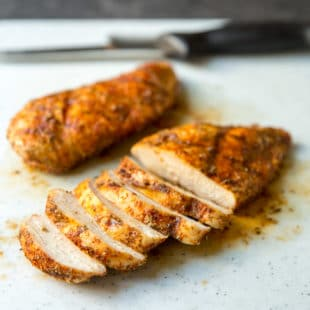 A closeup angled shot of sliced grilled chicken with rub.
