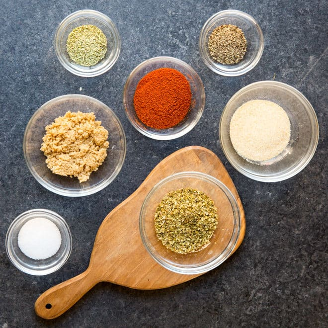 Grilled chicken rub ingredients in various bowls on a gray counter top.