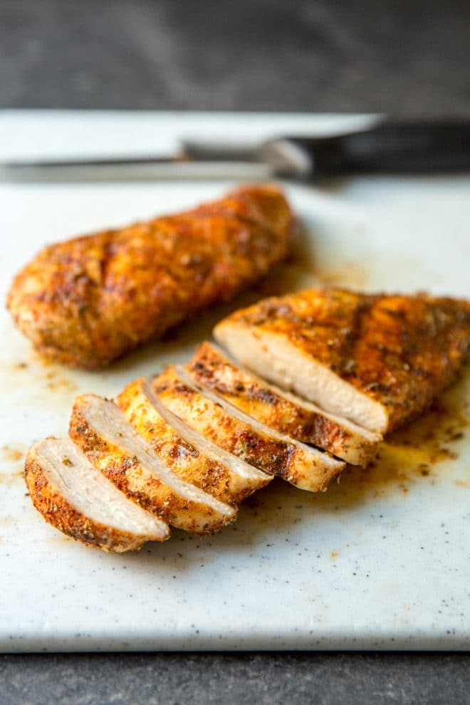 Sliced grilled chicken on a gray counter top.