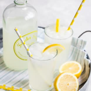 A closeup angled shot of how to make lemonade in two glasses on a silver tray.
