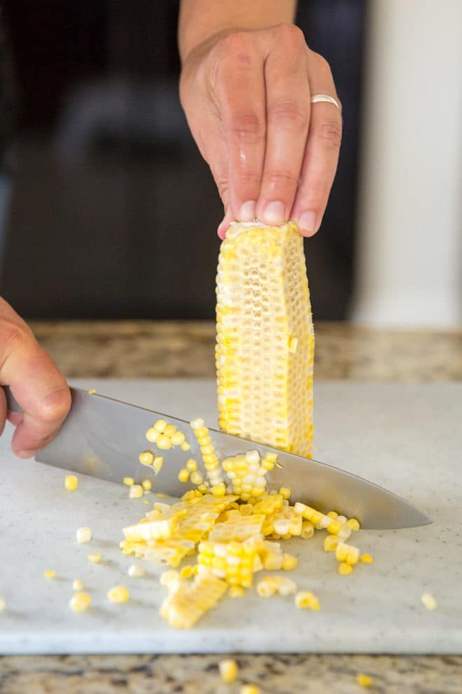 If you're finding corn kernels in hard to reach places all over your kitchen, it may be time to figure out a better way to handle summertime's favorite vegetable. Here's how to cut corn off the cob as neatly and efficiently as possible.