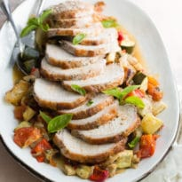 An overhead shot of pork loin with ratatouille on a white platter.