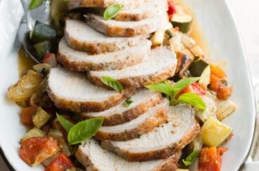 Pork loin with ratatouille on a white platter.