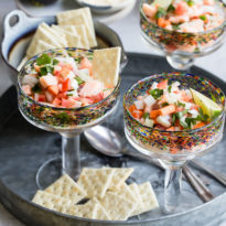 An angled shot of salmon ceviche in stemmed glasses.
