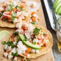 A closeup angled shot of shrimp ceviche on a wood cutting board.