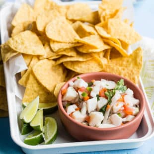 A closeup angled shot of taliapa ceviche in a pink bowl on a white platter with tortilla chips.