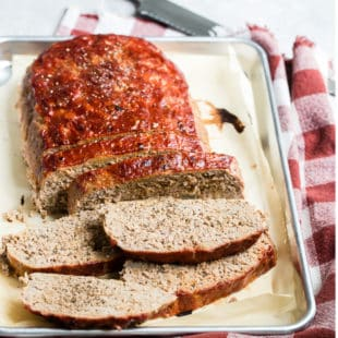 Sliced turkey meatloaf on a silver baking pan.