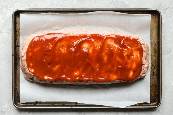 An overhead shot of sliced turkey meatloaf on a baker's sheet.