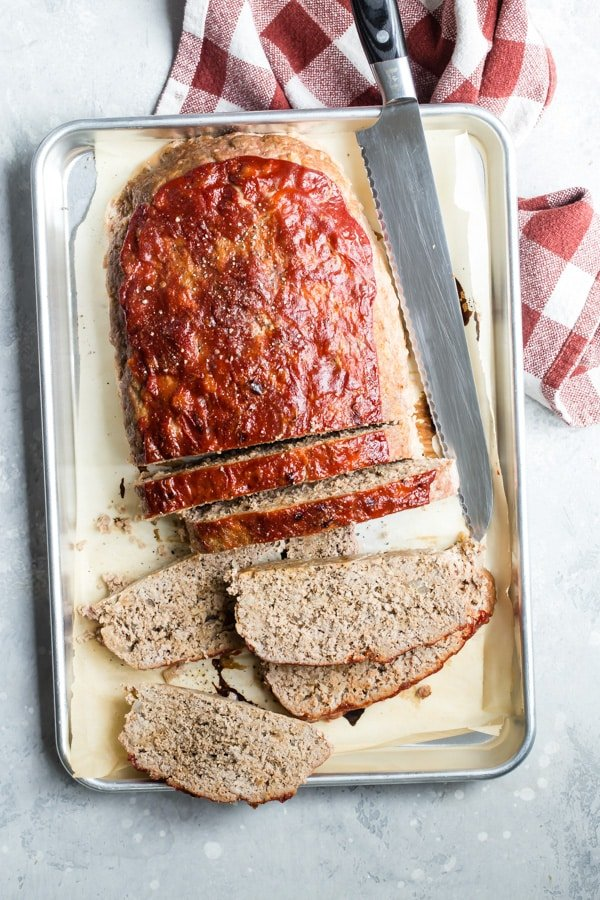 A side shot of sliced turkey meatloaf on a baker's sheet.