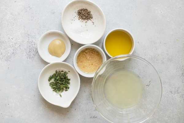 Lemon vinaigrette ingredients in various bowls on a gray counter top.