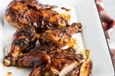 Barbecue chicken on a white platter.