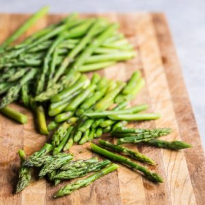 A closeup angled shot of chopped asparagus on a wood cutting board.
