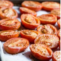 A closeup angled shot of roasted tomatoes in a baking pan.