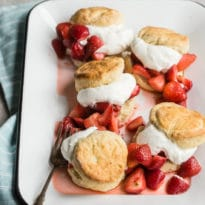Side shot of five strawberry shortcakes on a white platter.