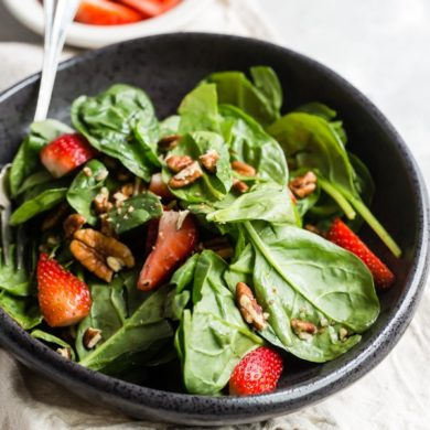 Strawberry spinach salad in a black bowl.