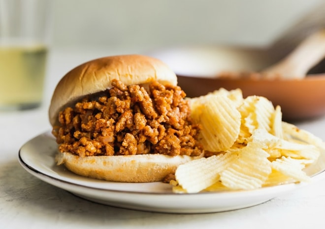 A side shot of a sloppy joe on a white plate served with potato chips.