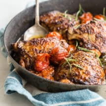 Balsamic chicken and tomatoes in a black dish.