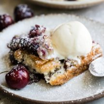 Cherry cobbler topped with ice cream and powdered sugar on a white plate.