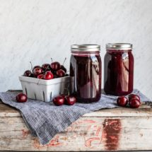 A side shot of cherries in a basket and two jars of canned cherries.