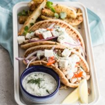 A closeup angled shot of chicken gyros in a white serving tray.