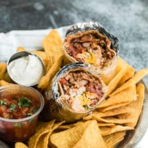 A chili cheese burrito cut in half with tortilla chips, salsa and sour cream in a silver platter.