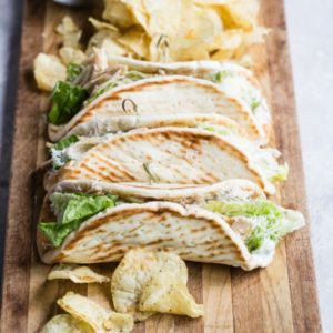 Grilled chicken Caesar wraps on a wood cutting board.
