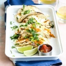 Grilled fish tacos with cabbage slaw on a white serving tray.