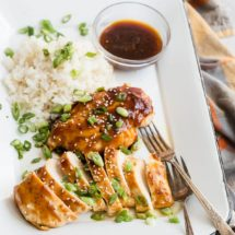 Honey garlic chicken with white rice and a clear bowl of sauce on a white serving platter.