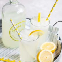 How to make lemonade in two clear glasses with yellow striped straws and a clear pitcher.