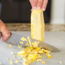Corn being cut off of the cob.