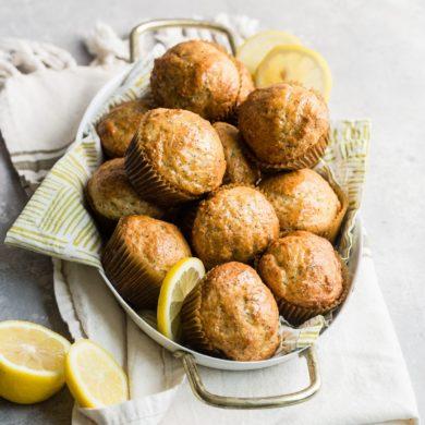 Lemon poppyseed muffins in a silver basket.