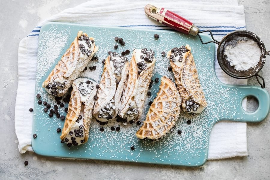 Mock italian cannolis with pizzelle on top of a blue cutting board covered in powdered sugar.