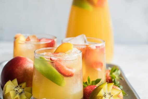 Passion fruit and pineapple sangria in three clear glasses on a silver platter.