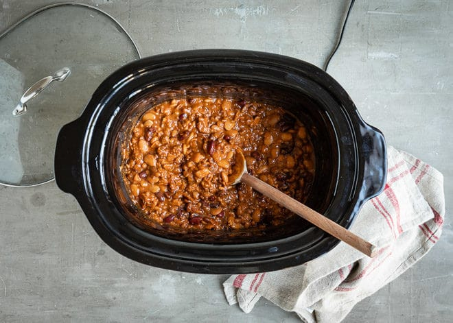 Slow cooker calico beans in a black slow cooker with a wooden spoon.