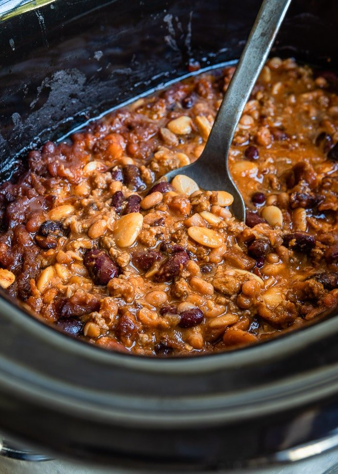 Slow cooker calico beans in a black slow cooker.