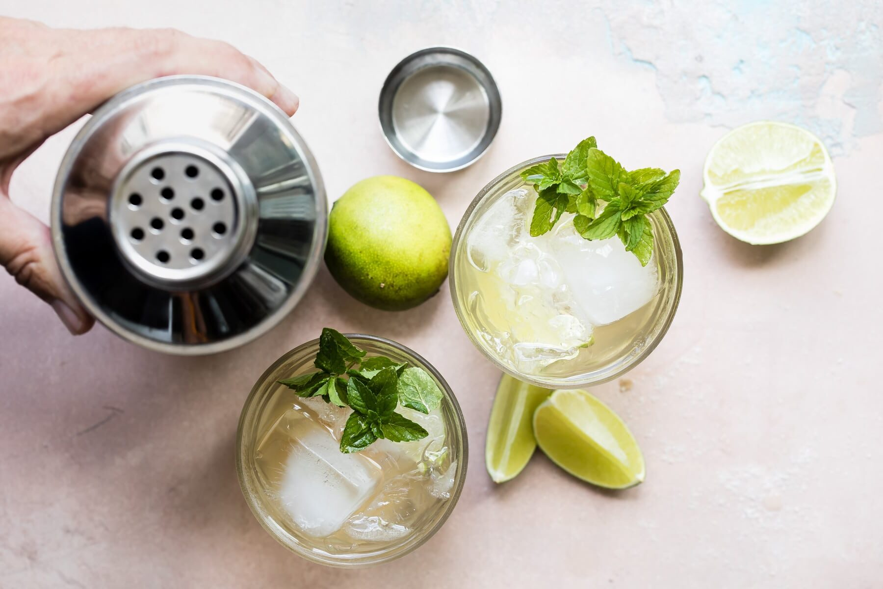 Two Moscow mules in clear glasses next to a cocktail shaker.