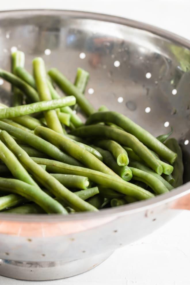 Green beans in a sliver colander.