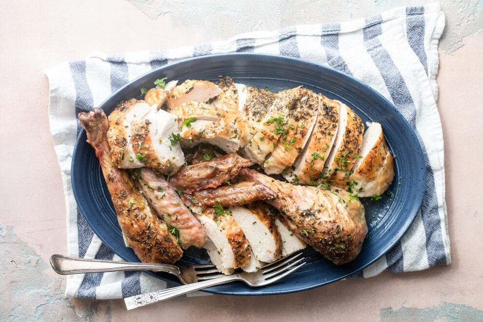 Make ahead roasted turkey on a blue platter with two silver forks.