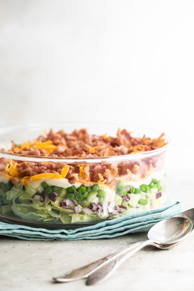 Seven layer salad in a glass dish.