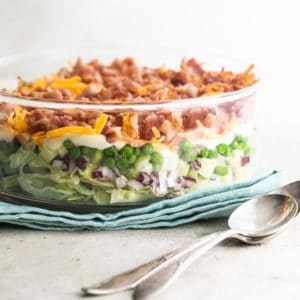 A closeup side shot of seven layer salad in a clear glass dish.