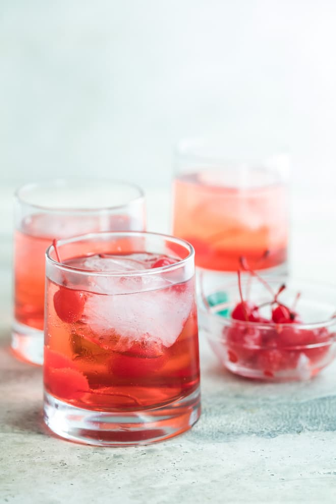 A side shot of Shirley temples in three clear glasses with a clear bowl filled with cherries.