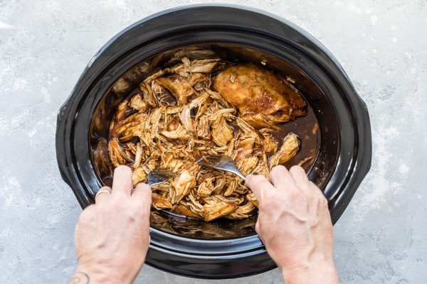 An overhead shot of slow cooker pulled chicken in a crockpot after being cooked.