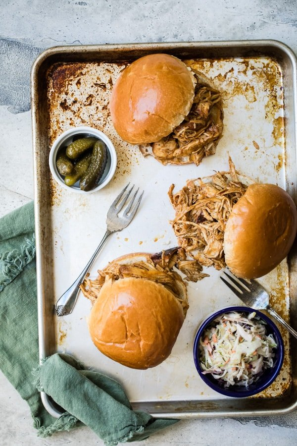 An overhead shot of three slow cooker pulled chicken sandwiches on a baking sheet.