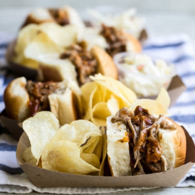 Slow cooker pulled pork sandwiches in trays with chips.
