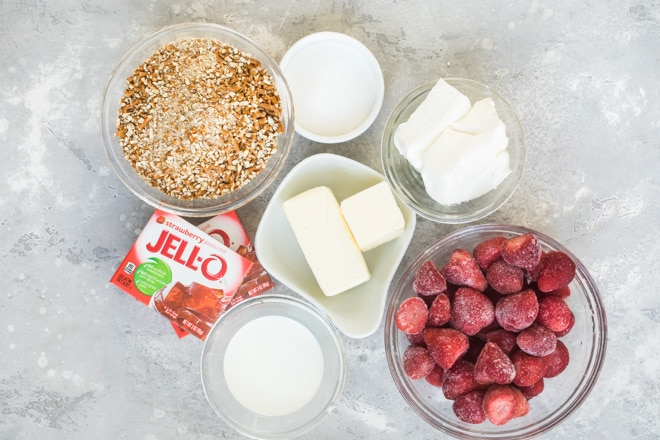 An overhead shot of strawberry pretzel salad ingredients in various bowls.