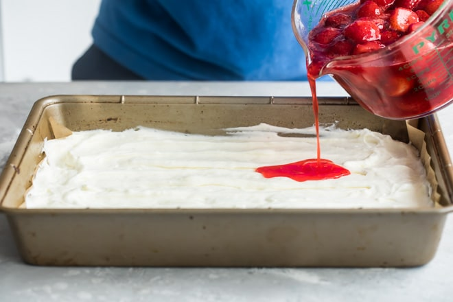 An angled shot of strawberries being poured onto the white filling into a tan baking pan.