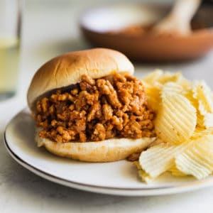 A sloppy joe on a white plate served with potato chips.