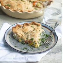 An angled shot of turkey pot pie in a white pie pan and a piece of turkey pot pie on a blue plate with a fork and a clear glass of water.