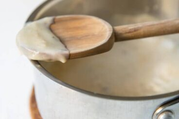 Condensed cream of chicken soup on a wooden spoon resting on a silver pot.